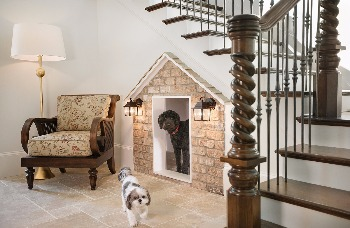 custom dog house with lamps and fake siding on the front, built into a wall underneath a stairway